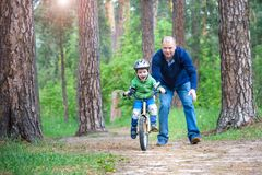 Little kid boy of 3 years and his father in autumn forest with a Stock Image