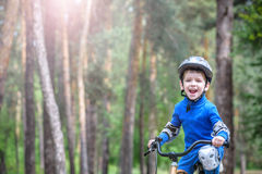 Little kid boy of 3 years and his father in autumn forest with a bicycle. Dad teaching son. Man happy about success. Child helmet. Royalty Free Stock Images