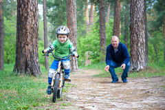 Little kid boy of 3 years and his father in autumn forest with a bicycle. Dad teaching son. Man happy about success. Child helmet. Royalty Free Stock Image