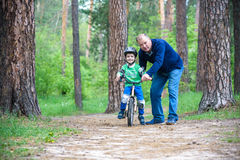 Little kid boy of 3 years and his father in autumn forest with a bicycle. Dad teaching son. Man happy about success. Child helmet. Stock Image