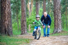 Little kid boy of 3 years and his father in autumn forest with a Royalty Free Stock Photo
