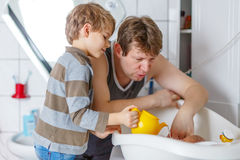 Little kid boy and young father bathing newborn baby Royalty Free Stock Photo