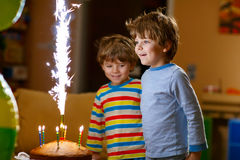 Little kid boys celebrating birthday with cake and candles. Beautiful kids, little boys celebrating birthday and blowing candles on homemade baked cake, indoor Royalty Free Stock Photos
