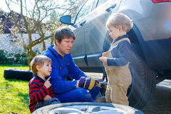 Little kid boys and his father changing wheel on car Royalty Free Stock Photos