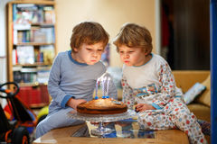 Little kid boys twins celebrating birthday and blowing candles on cake Stock Photography