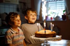 Little kid boys twins celebrating birthday and blowing candles on cake Stock Images