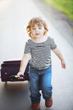 Little kid carrying a suitcase. Relocation or travelling with children. Stock Photo