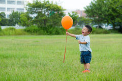 Little kid catch with flying balloon. Asian young little boy at outdoor stock photo