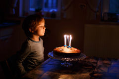 Little kid celebrating his birthday and blowing candles on homem Royalty Free Stock Photo
