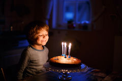 Little kid celebrating his birthday and blowing candles on homem. Adorable five year old kid celebrating his birthday and blowing candles on homemade baked cake Royalty Free Stock Photo