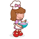 Little kid chef cooking. A little girl wearing a chef uniform and cooking Stock Photo