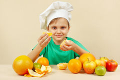 Little kid in chefs hat peeling fresh orange at table with fruits Stock Images