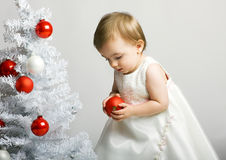 Little kid with a christmas tree Stock Images