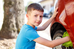 Little kid cleaning car wheel Royalty Free Stock Photography