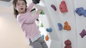 Little kid climbes a rock wall stock video