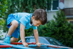 Little kid climbing on jungle gym without rope and helmet Stock Images
