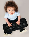 Little kid with a computer keyboard Royalty Free Stock Images