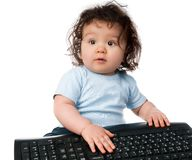 Little kid with a computer keyboard Stock Images