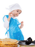 Little kid cooking pancakes. Girl gesturing good or delicious. Isolated on a white background Stock Photo