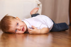 Little kid crying. Lying on floor Royalty Free Stock Photography