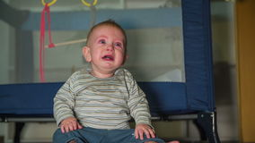 Little kid crying his lung out. On this slow motion high quality footage of a small baby boy crying his lungs out and sitting in front the crib stock video