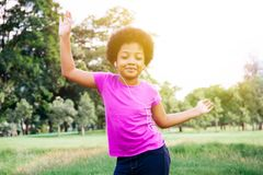 Little kid dancing and listening to music in green park Royalty Free Stock Photo