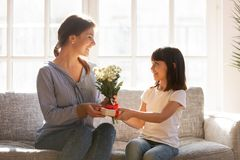 Free Little Kid Daughter Giving Mom Receiving Gift Box And Flowers Stock Photos - 139193543