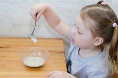 Little girl eating porridge. A little kid doesn`t like porridge royalty free stock image