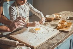 Little kid doing his first dough. Dad teaching son smashing eggs. Boy pouring egg into the flour. Cooking implements on table Stock Photography