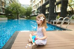 Little kid doing yoga exercises sitting close to swimming pool w royalty free stock photo