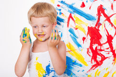 Little kid draws bright colors. School. Preschool. Education. Creativity. Studio portrait over white background Royalty Free Stock Photo