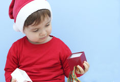 Little kid dressed as santa claus with a gift Stock Photography