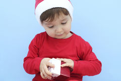 Little kid dressed as santa claus with a gift Royalty Free Stock Image