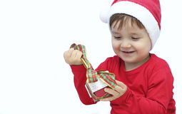 Little kid dressed as santa claus with a gift Stock Photo