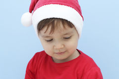 Little kid dressed as santa claus looking down Royalty Free Stock Image