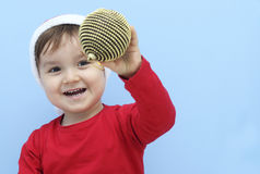 Little kid dressed as Santa Claus showing a golden bauble Stock Image