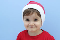 Little kid dressed as santa claus smiling Stock Photo