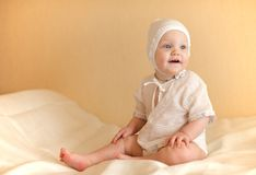Little kid dressed in white sits on the bed smilin Stock Photos