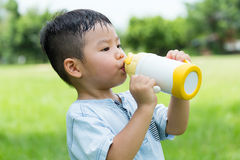 Little kid drink of water bottle. Asian young little boy at outdoor stock images
