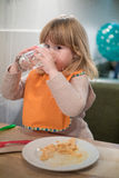 Little kid drinking water glass at pizza restaurant looking Stock Photography