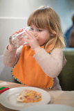 Little kid drinking water glass at pizza restaurant Royalty Free Stock Photography