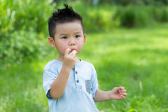 Little kid eating with snack Stock Images