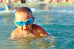 Little kid emerges from the sea water Stock Photos