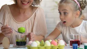 Little kid excitedly watching mom dying egg in green food coloring, Easter decor. Stock footage stock video