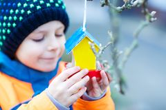 Little kid hanging bird house on tree for feeding in winter Royalty Free Stock Images