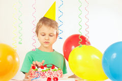 Little kid in festive hat looking at birthday cake Royalty Free Stock Image