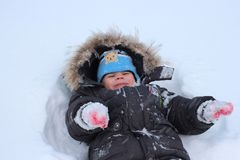 Little kid laughing winter fell in the snow having fun royalty free stock images