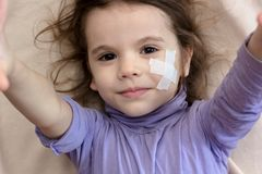 Little kid girl with adhesive band on face making selfie. Little kid girl with adhesive band on face making selfie royalty free stock image
