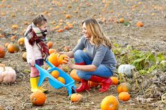 Little kid girl and beautiful mother having fun with farming on a pumpkin patch. Traditional family festival with. Children, thanksgiving and halloween concept stock photography