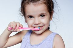 Little kid girl cleaning teeth by toothbrush, dental care concept. Little kid girl cleaning teeth by toothbrush, dental care concept royalty free stock image